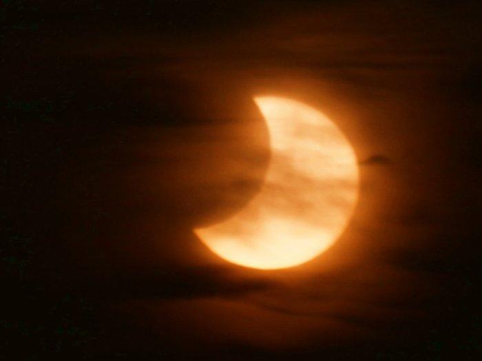 El Sol entre nubes eclipasado parcialmente por la Luna